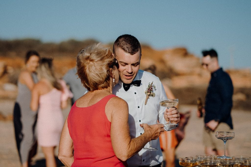 older woman in red dress giving groom a kiss on the cheek