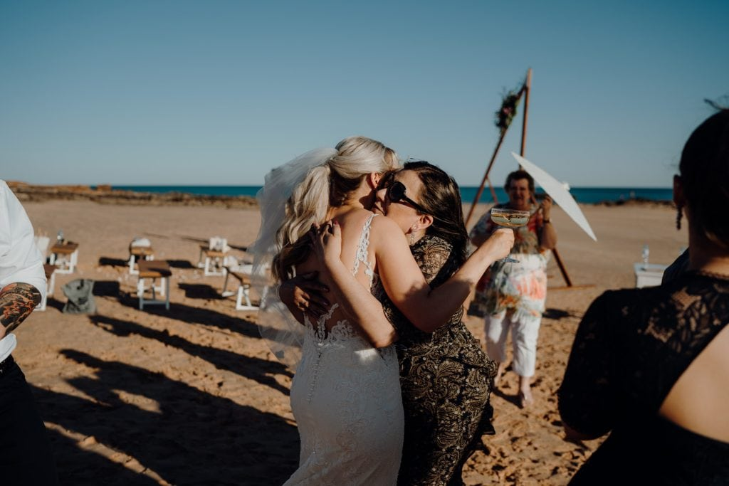 wedding guests embraces the bride in a big hug at her beach wedding