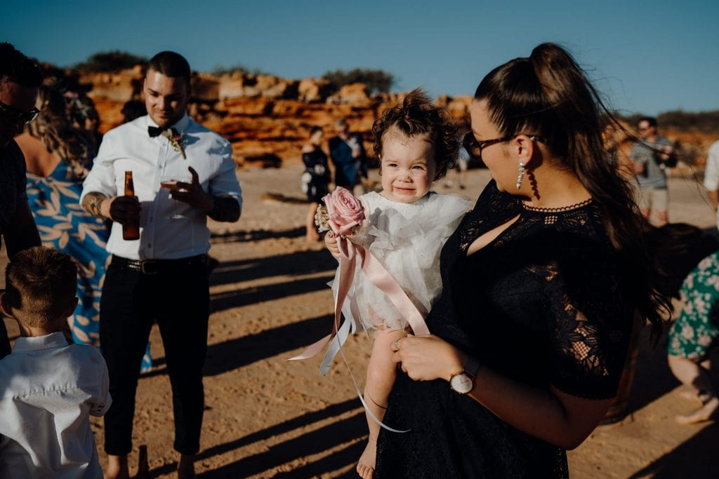 little girl in white dress in the arms of a woman at relaxed beach wedding