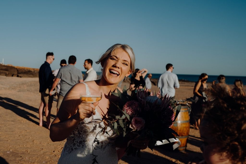 laughing bride with Champagne glass and flower bouquet