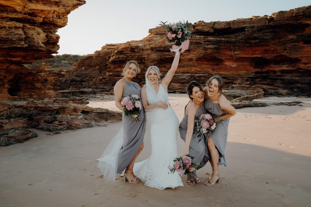 bride and her three bridesmaids having fun on the beach at relaxed Broome wedding