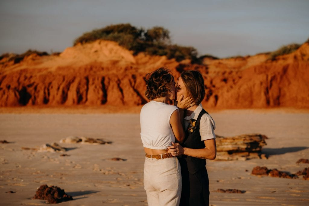 two women kissing on beach with red cliffs