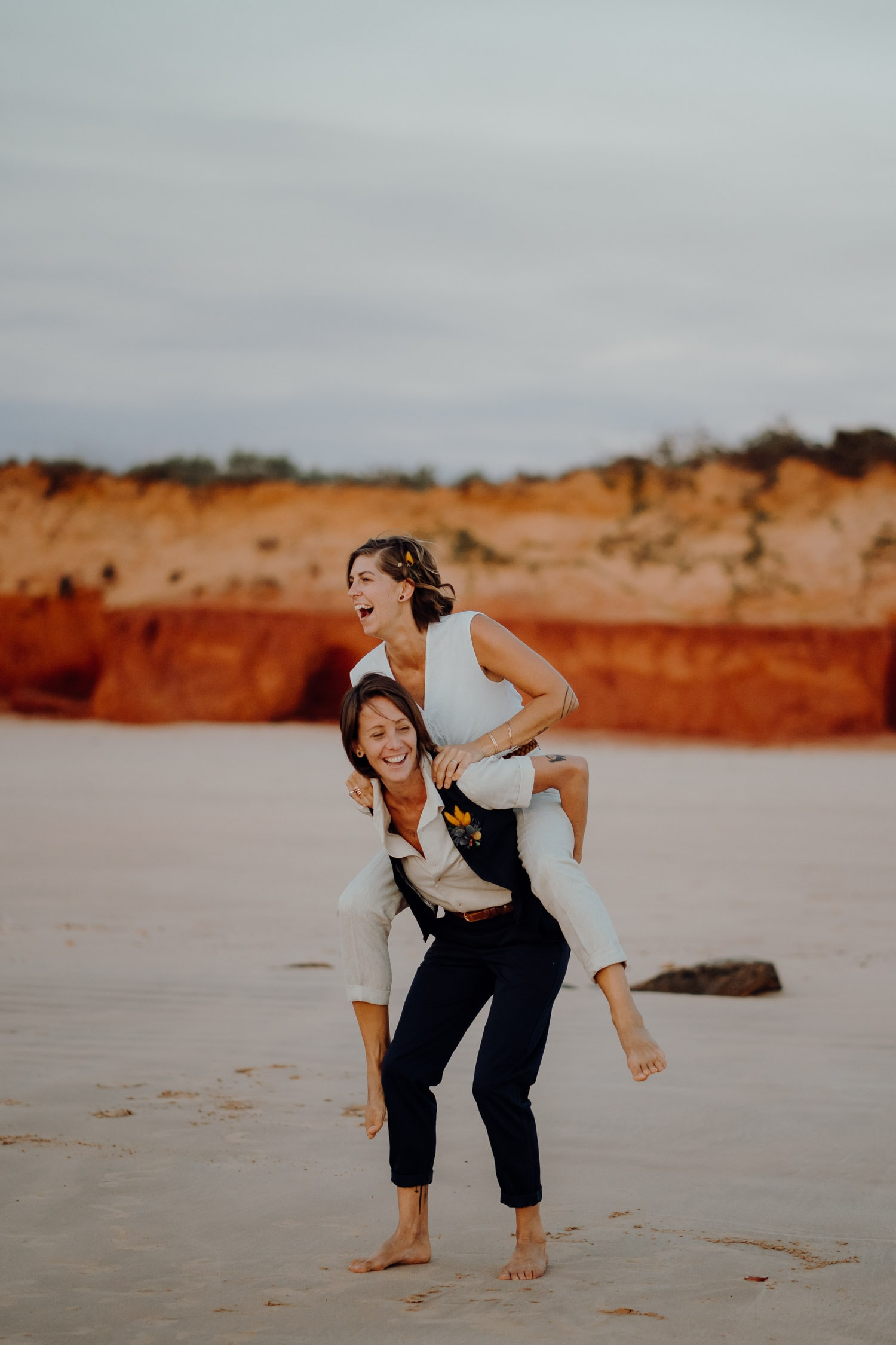 women piggybacks another woman at Broome elopement wedding