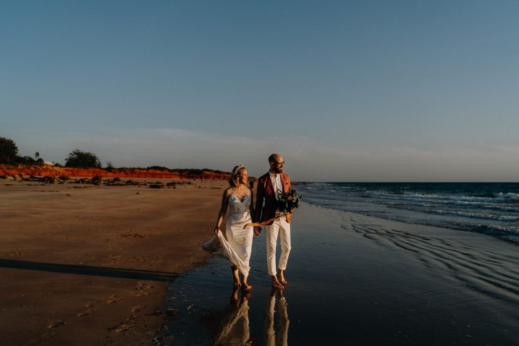 young couple walking along the beach in wedding attire and with flower bouquet