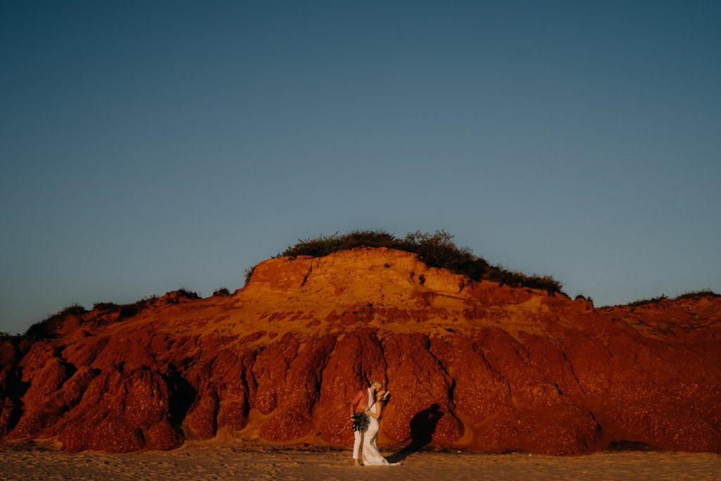Broome Elopement Wedding Broome Western Australia couple kissing in front of large red cliff