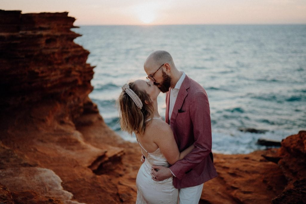 Broome elopement wedding couple kissing among the red rocks at Gantheaume Point with ocean views