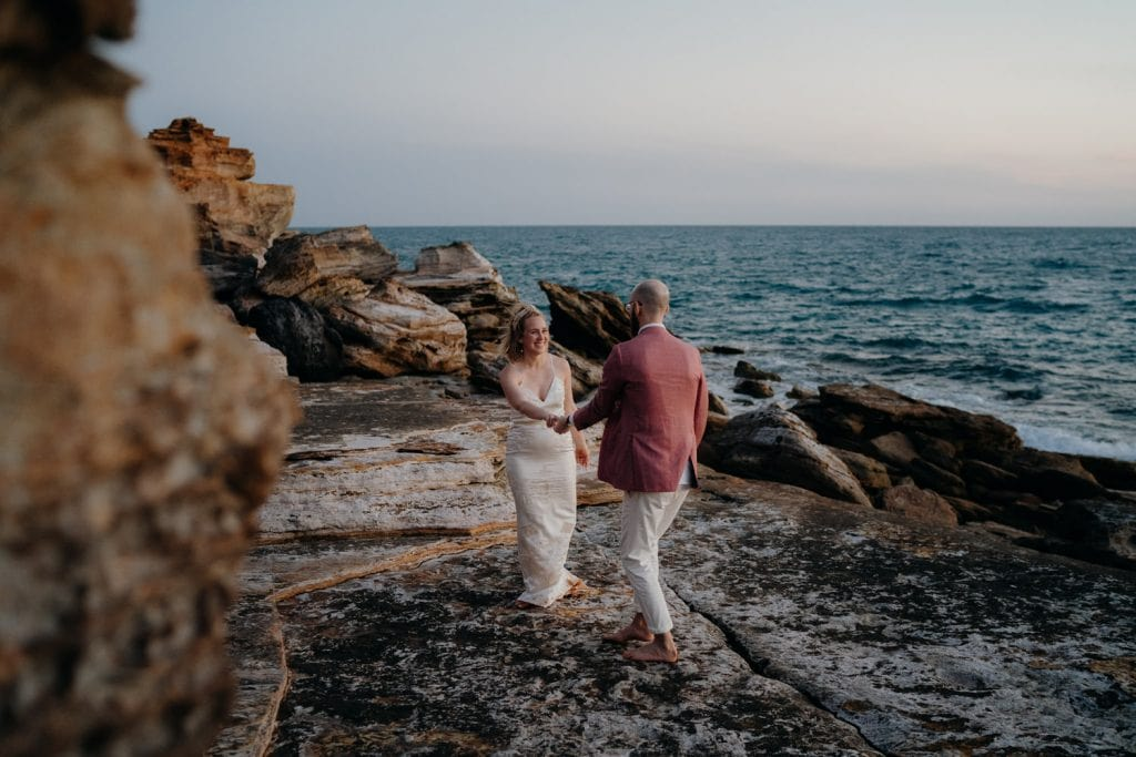 bride and groom dancing on a large flat rock at their Broome elopement wedding with ocean behind them