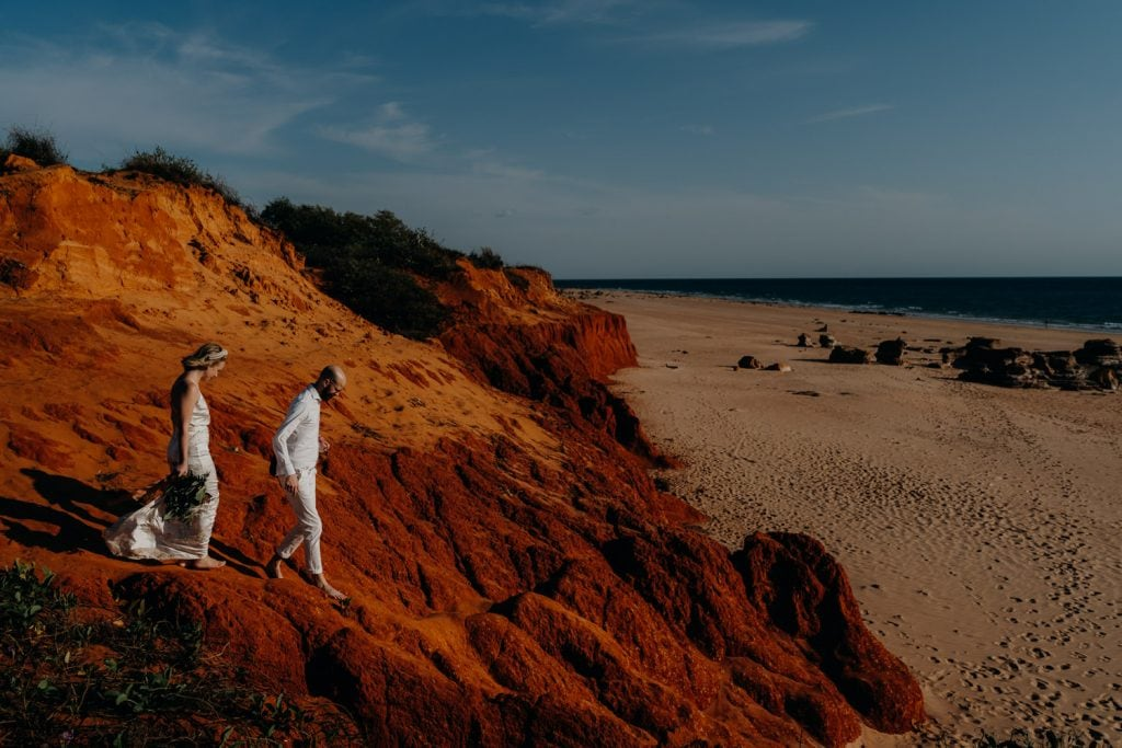 wedding couple walking down a red cliff to their Broome elopement wedding on Reddell Beach