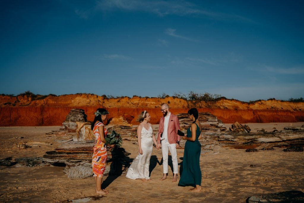small Broome elopement on quiet beach with red cliffs as a backdrop and one guest