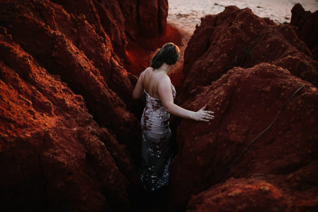 woman in summer dress scrambles down a cliff