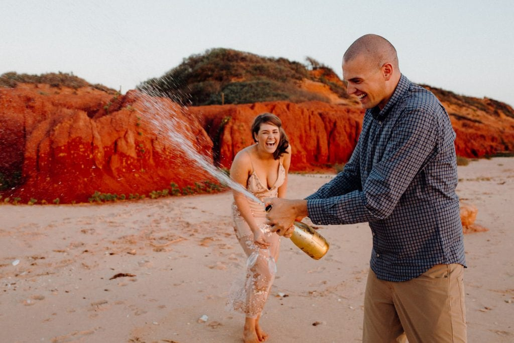 young laughing couple on the beach with champagne bottle