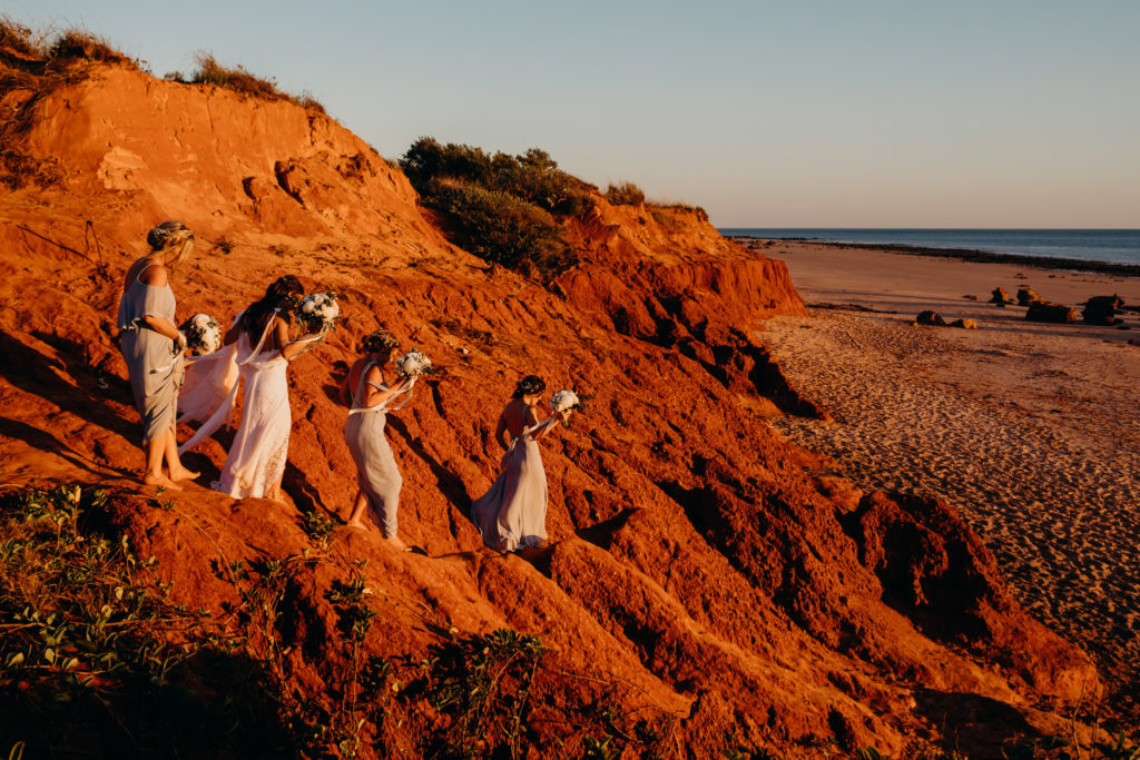group of women in beautiful dresses walks down red cliff at Riddell Beach in Broome
