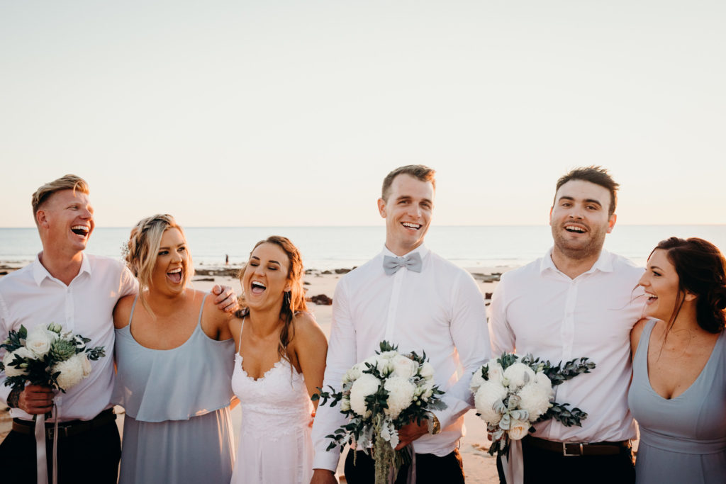 bridal party on the beach with the sun setting behind them