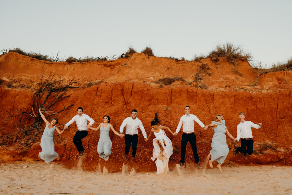 bridal party jumps in the air in front of red cliff in Broome