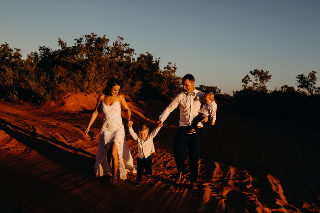 young family walks in the red Kimberley earth on their wedding day with their two small children