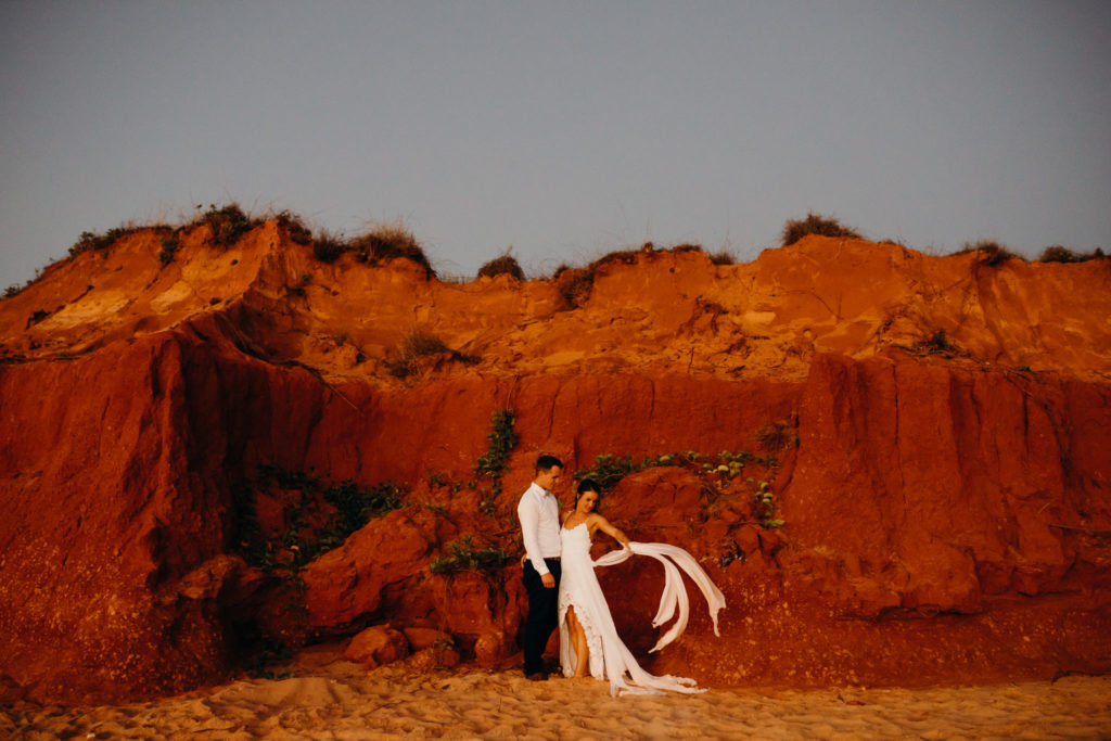 Broome Fishing Club wedding with bride and groom standing in front of red cliffs on beach