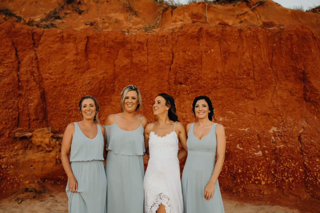 Kimberley bride with three of her bridesmaids in front of red cliffs in Broome near the Fishing Club