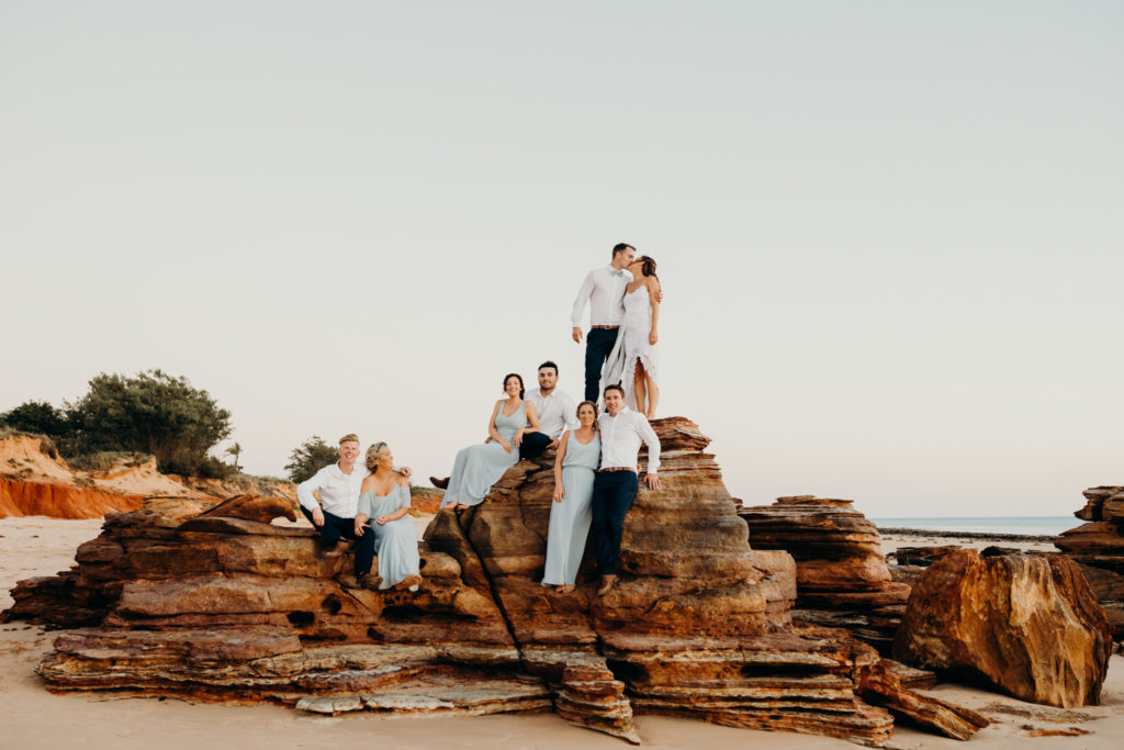 wedding group sits on rocks