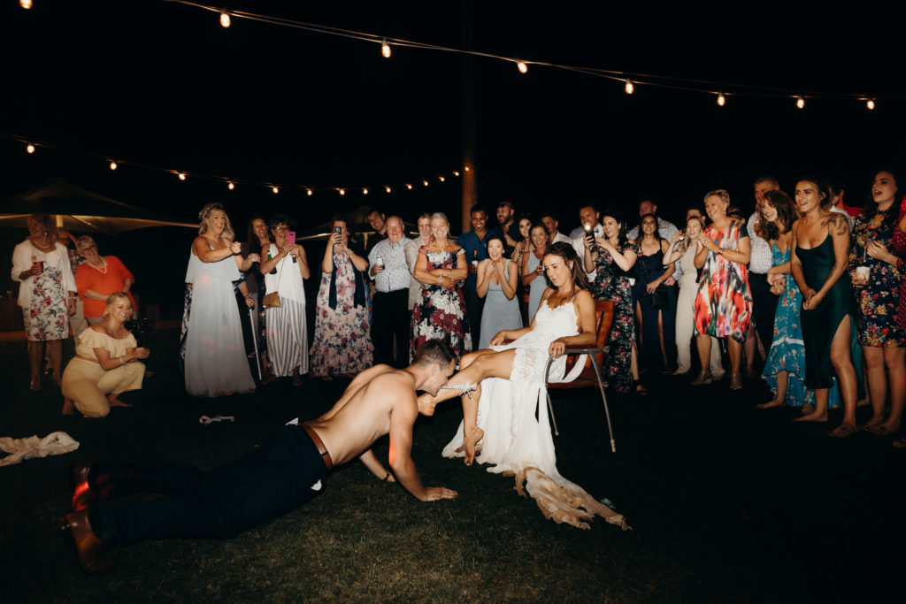 groom stripped off his shirt and dances around his bride who is sitting on a chair under the stars