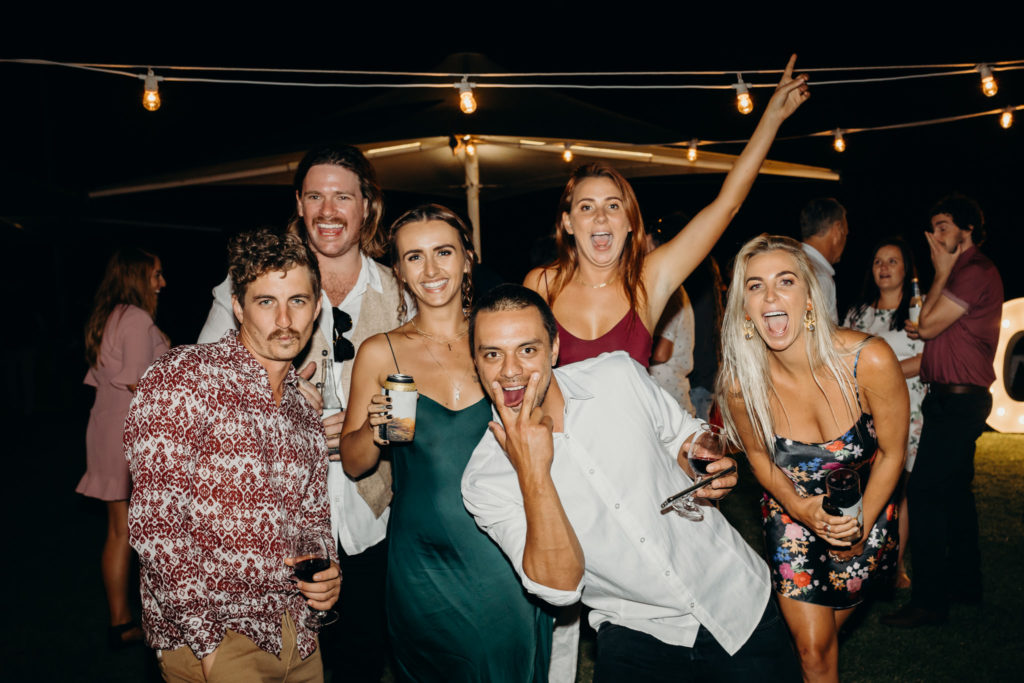 group of wedding guests pulling faces and laughing at the camera
