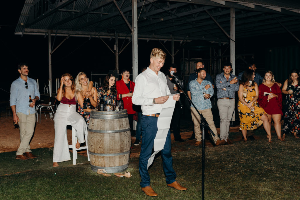 best man gives at speech at Broome Fishing Club wedding with long piece of paper