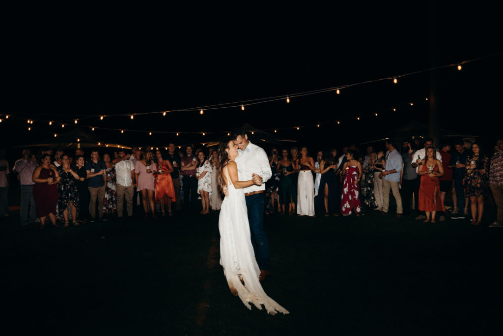 bride and groom having their first dance at the Broome Fishing Club with festoon lighting and wedding guests in the background