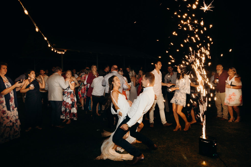 bride and groom dance off with sparkler machine