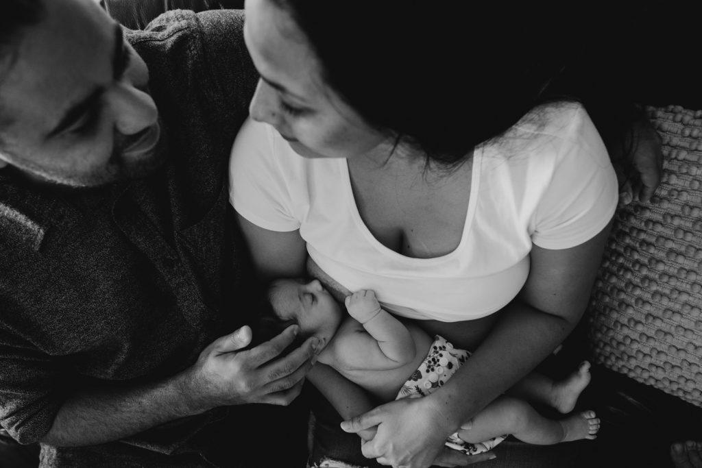 young Yawuru Aboriginal family sitting at home with newborn baby breast feeding
