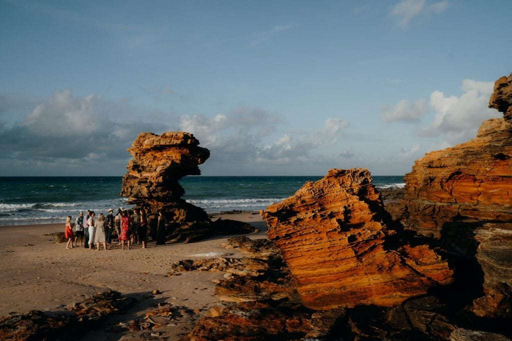 wide shot of small wedding at beach with red rocks glowing in the sunrise light