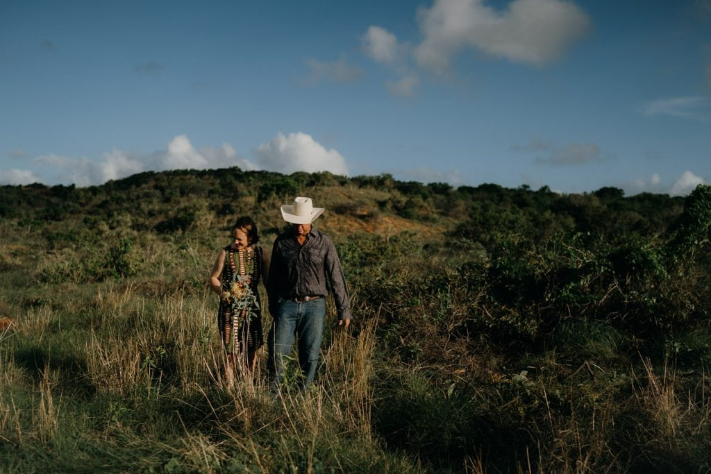 man wearing cowboy hat and woman in green dress walk through the scrub