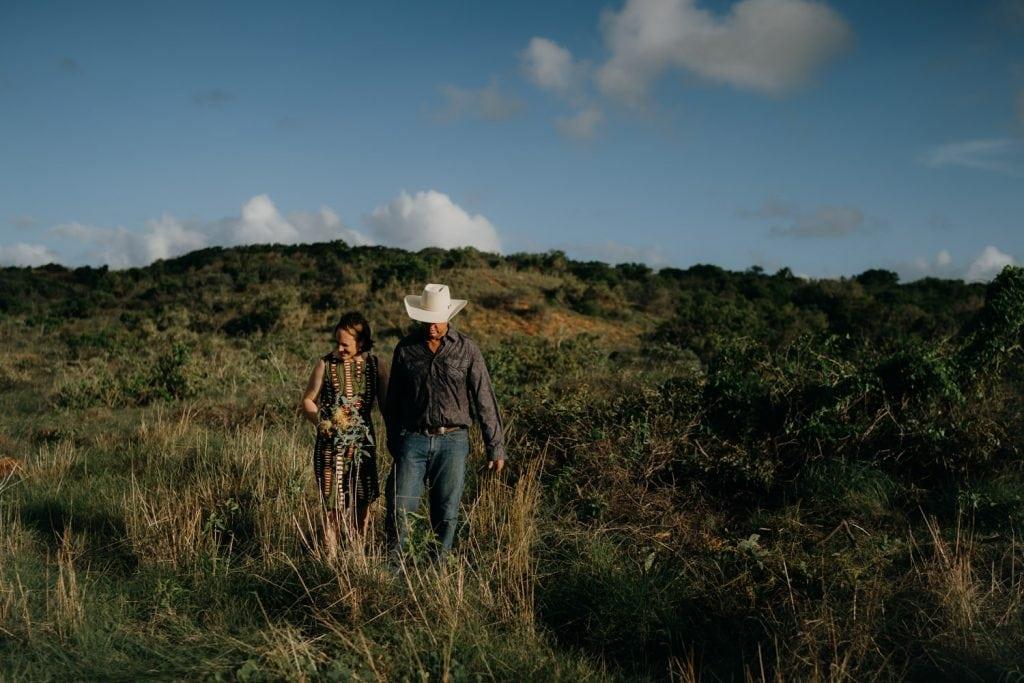 man wearing cowboy hat and woman in green dress walk through the scrub