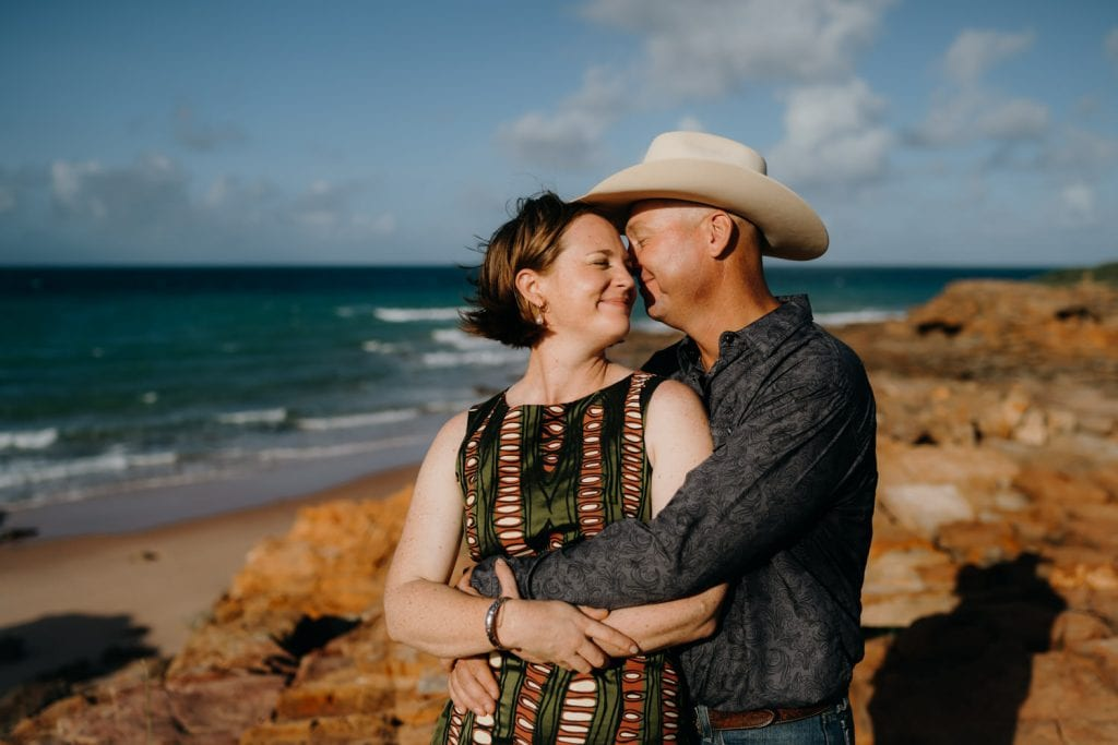 man with large hat has his arms around his wife with ocean and rocks in the background
