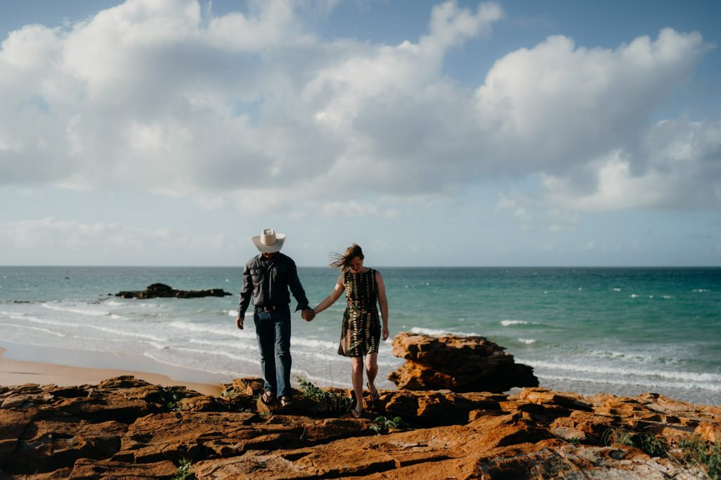 newly married couple walks hand in hand across red rocks at their Broome sunrise wedding