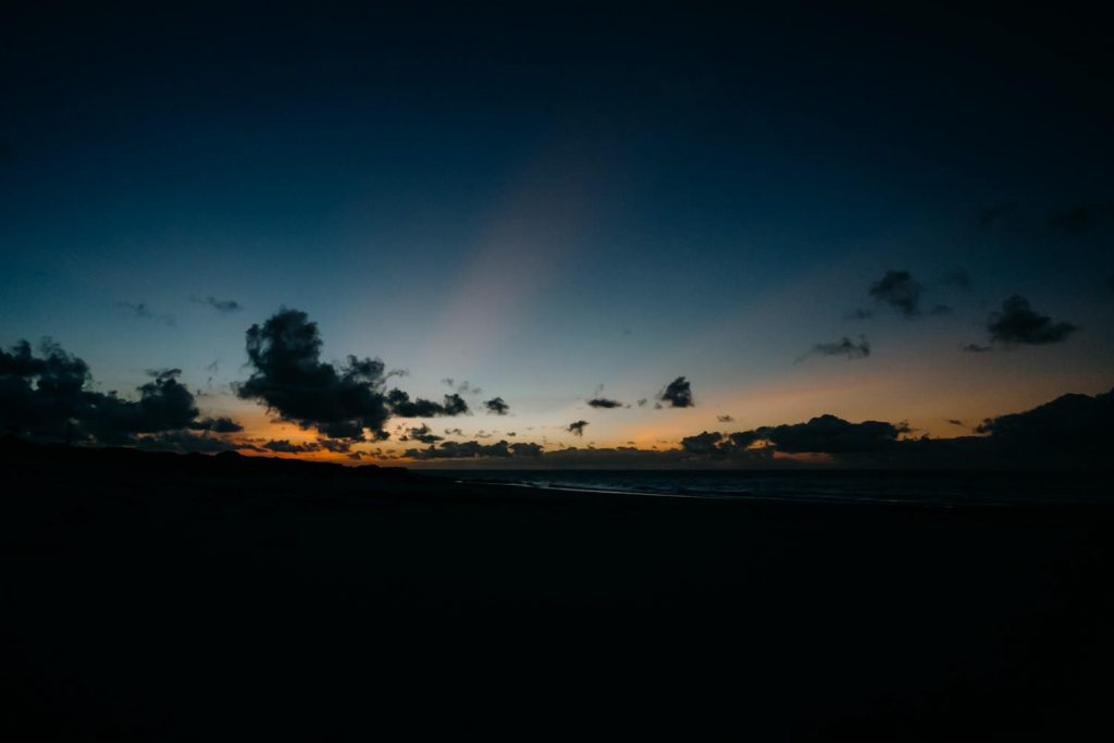 sunrise at beach wedding in Broome with sun beams in clouds