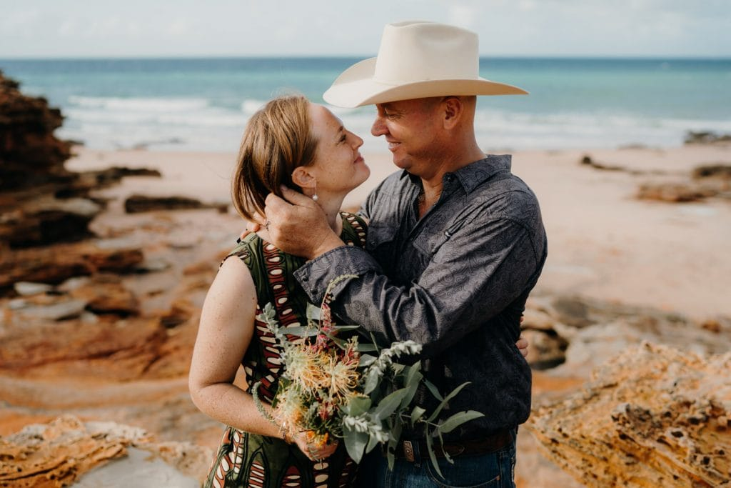 man with large cowboy hat lovingly holds women close to him and looks into her eyes