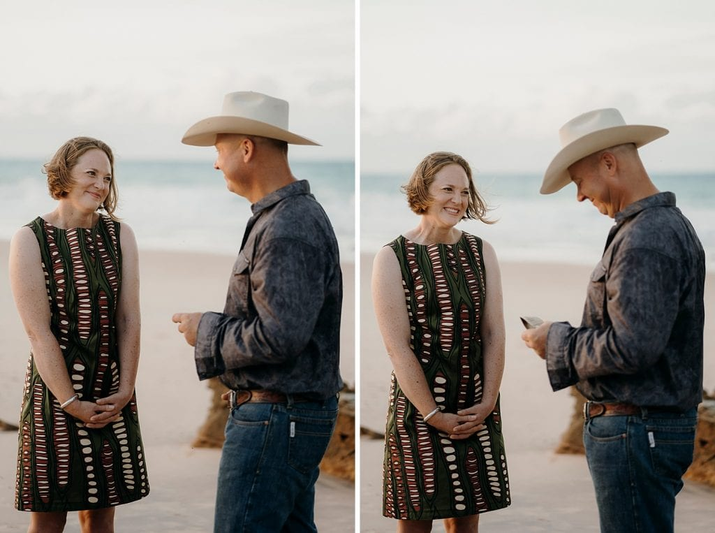 groom wearing cowboy hat reads his vows to his bride