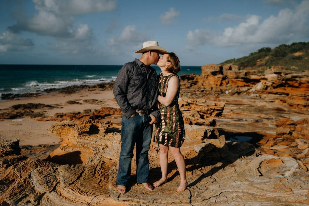 kissing couple standing on rocks near the ocean soon after their sunrise wedding in Broome at Entrance Point beach