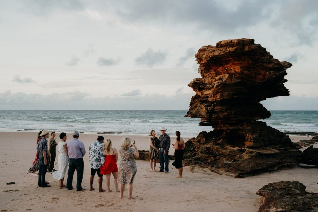 wedding guests are gathering around large rock by the water at sunrise beach wedding in Broome
