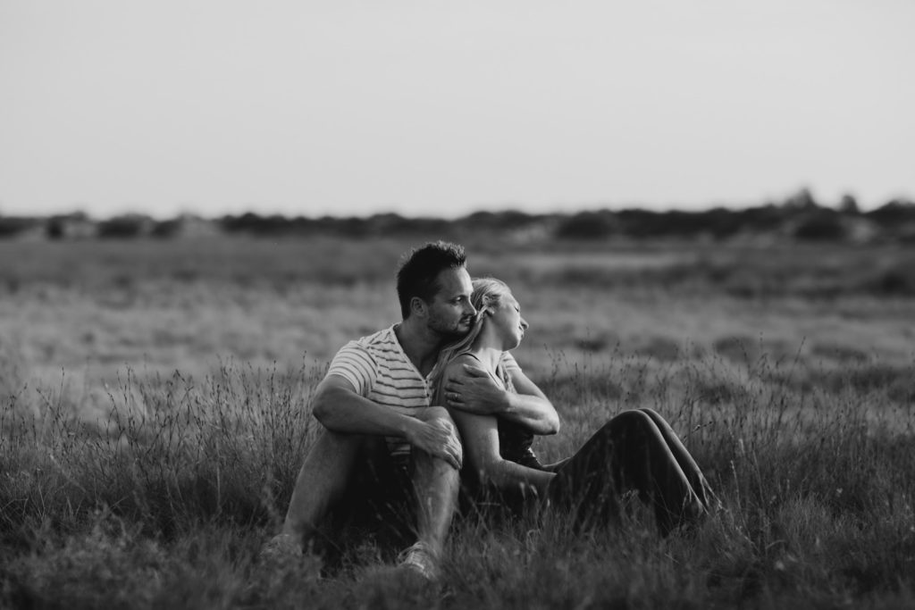 black and white photo pf young couple sitting together in the grass with their eyes closed