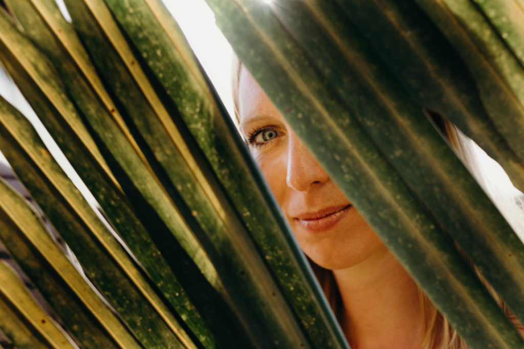 young woman looks through palm leaves during her couple shoot