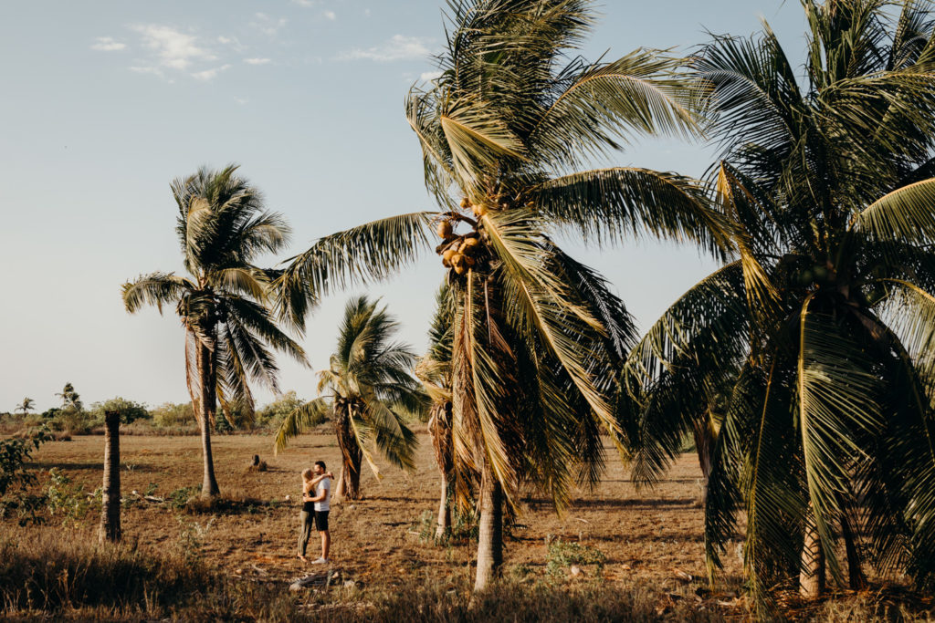 young couple stands in between coconut palms and kiss each other north of Broome
