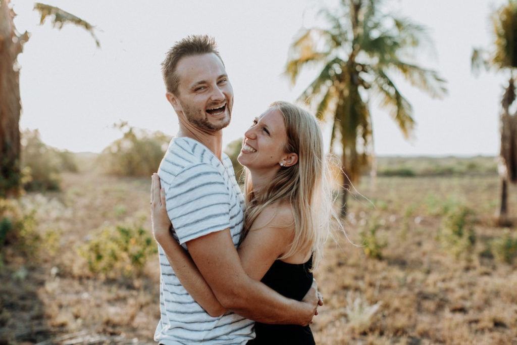 young couple hugging each other during couple shoot and laughing with palm trees in the background