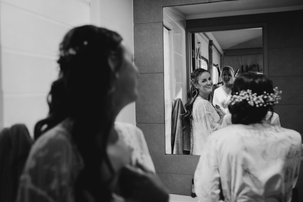 young bride sees herself in the mirror at the getting ready for her Broome Fishing Club wedding