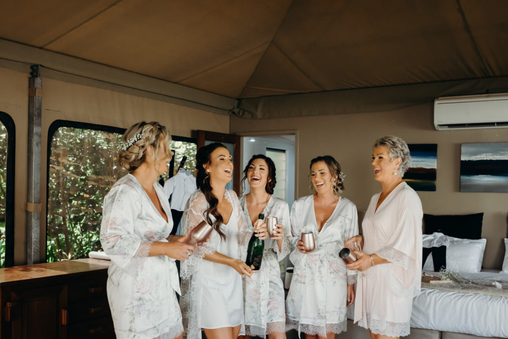 bride and her bridesmaids drinking champagne at Billi Resort safari tent