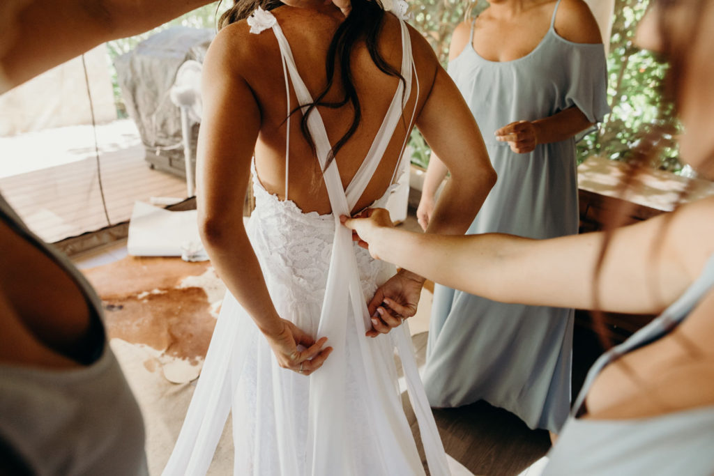 young woman is getting into her wedding dress with bridesmaids hands holding together the back straps