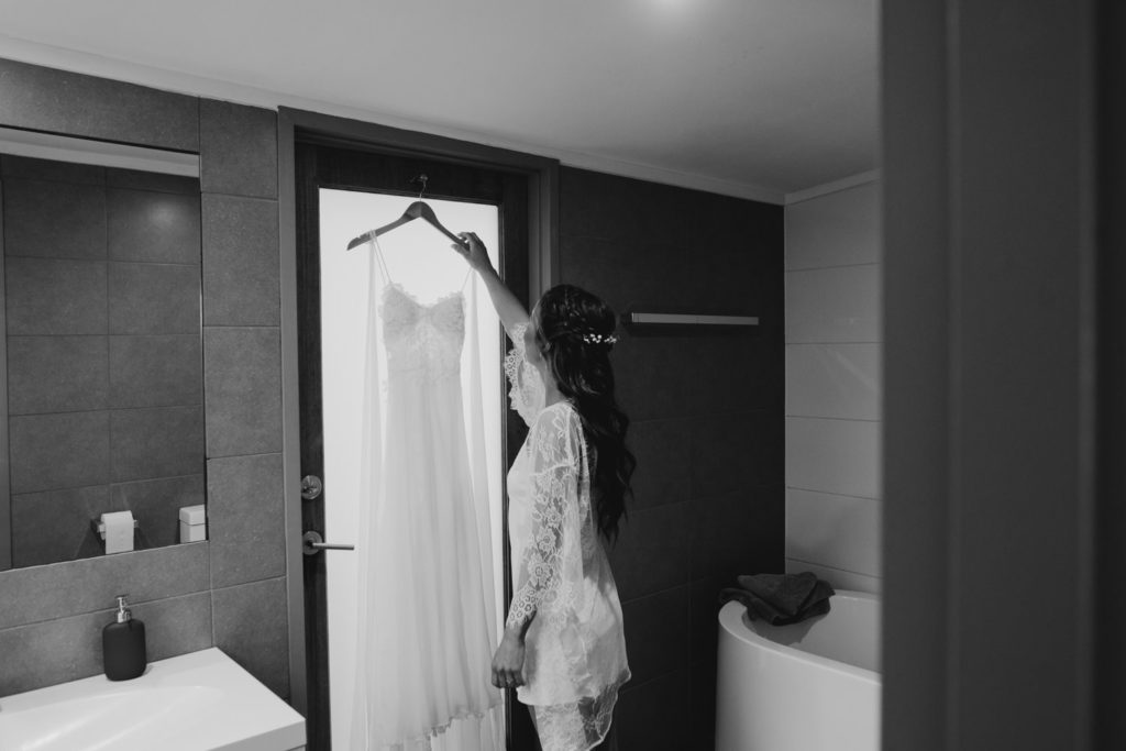 bride in the hotel bathroom with her wedding dress
