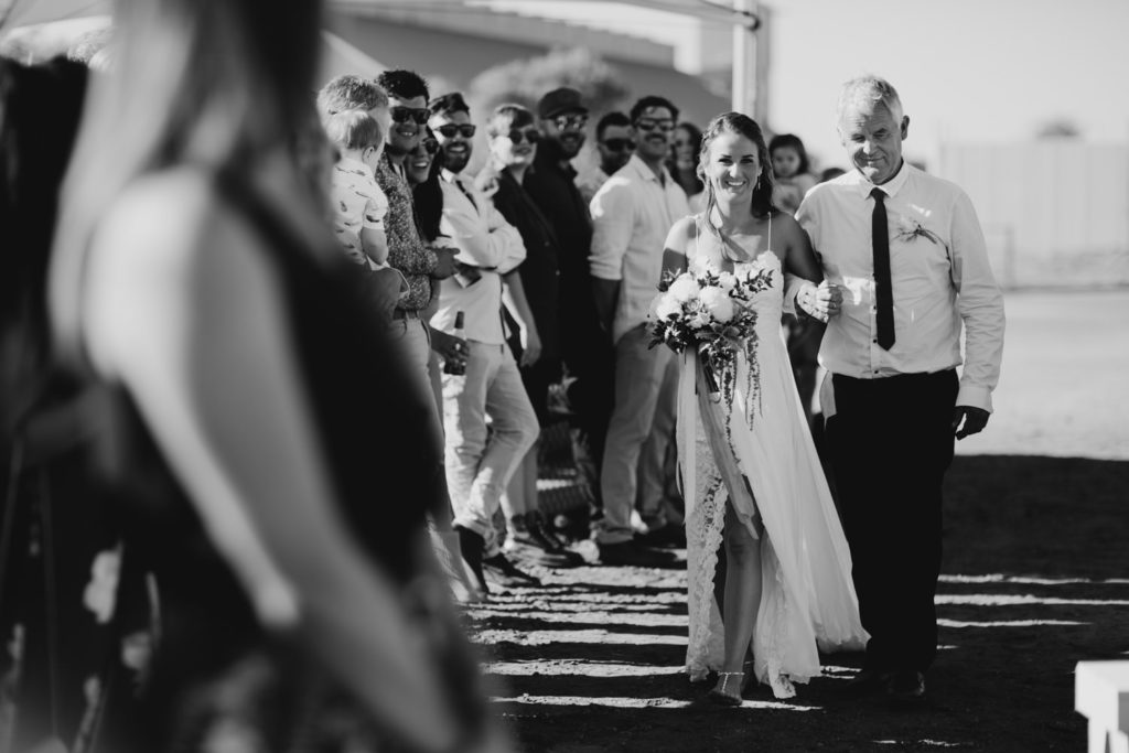 black and white photo of father and bride walking down the ailse