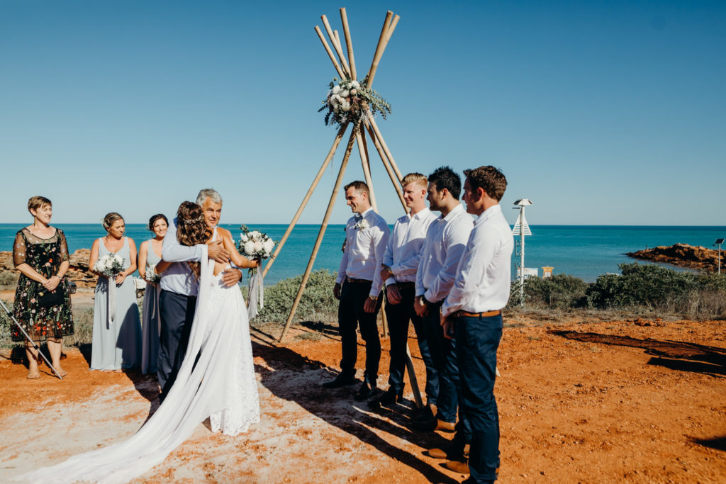 the father of the bride hugs his daughter before giving her away at Broome Fishing Club wedding
