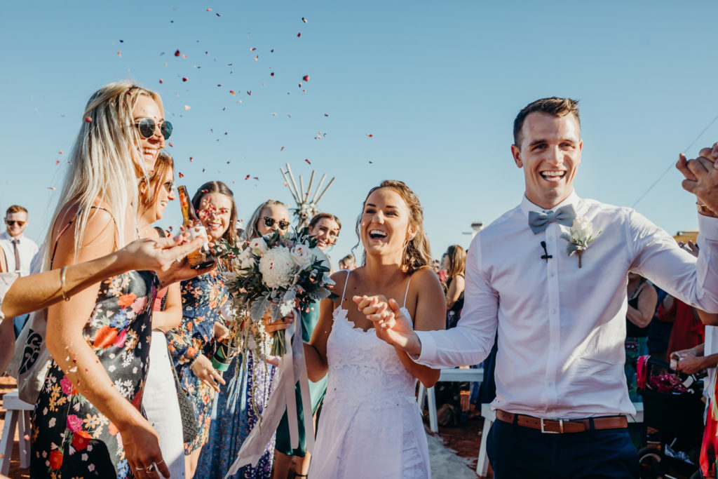 young wedding couple walks back down the aisle with flower petals being thrown by wedding guests at Broome Fishing Club