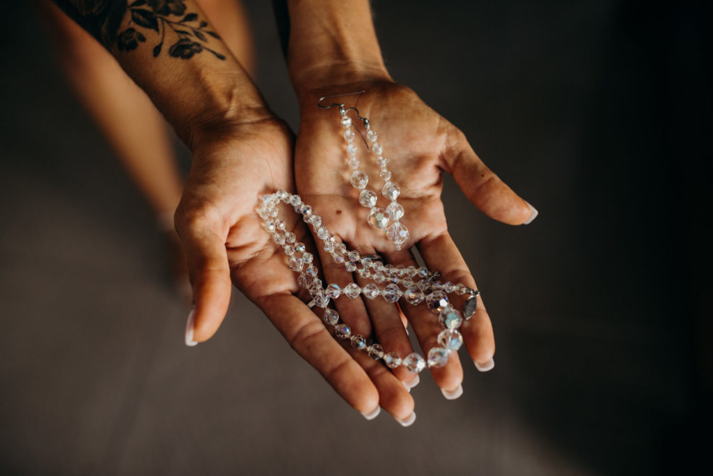 close up of women's hands holding jewellery for Riddell Beach wedding